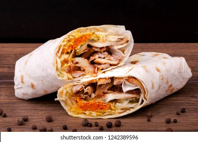 Shawarma sandwich gyro fresh roll of lavash (pita bread) chicken beef shawarma falafel RecipeTin Eatsfilled with grilled meat, mushrooms, cheese. Traditional Middle Eastern snack. On wooden background