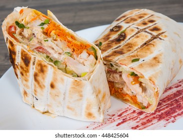 shawarma in thin pita bread with chicken and vegetables on a plate