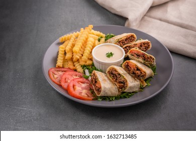 Shawerma beef meal Arabic style, served with fries, pickles, tomatoes and tahini sauce