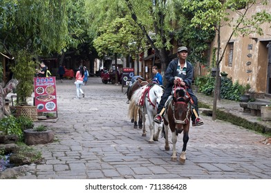 Shaxi China Sep 13 2016, man riding horse in street leading other horses