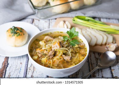 Shchi (cabbage soup) with buns (pampushki), fat and garlic. Traditional Russian and Ukrainian soup. Selective focus, close-up.