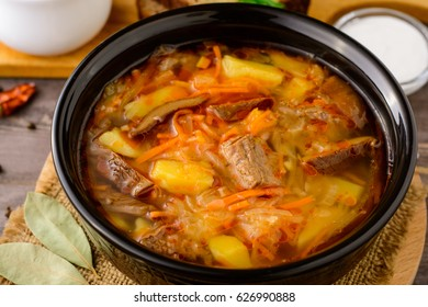 Shchi - traditional russian cabbage soup on wooden table.