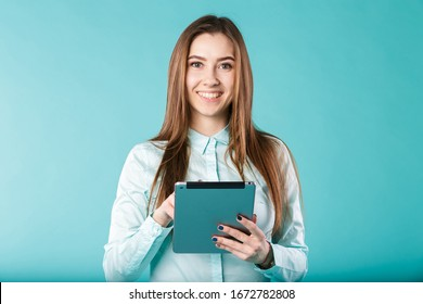 She always connected. Woman using digital tablet computer PC happy isolated on turquoise background. Portrait young caucasian woman worker, teacher, mentoring in shirt office style with tablet in hand