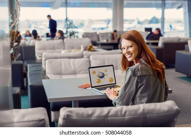 She always travels with tablet. Beautiful girl enjoying her laptop while sitting in airport lounge hall, looking at camera and smiling