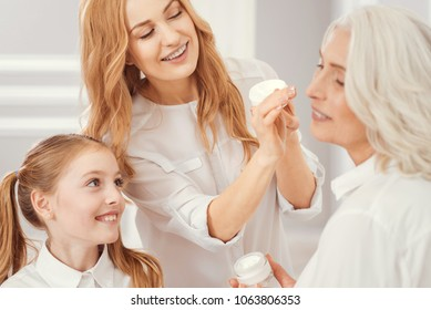 She is so beautiful. Selective focus on thoughtful grandchild and mother smiling while applying an anti aging cream on a face of their charming grandmother at home.