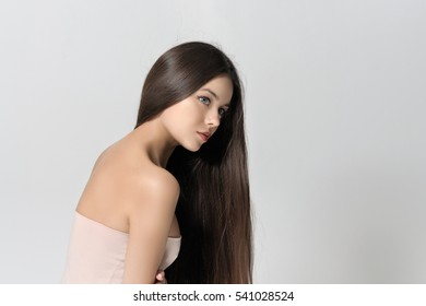 She covered her face with hair. Beautiful woman with bare shoulders has a clean well-groomed skin and long straight hair. Close-up portrait against a light gray background.