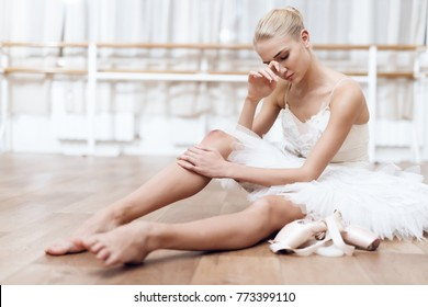 She is dressed in a ballet tutu. She is the professional theater actor. She is tired.