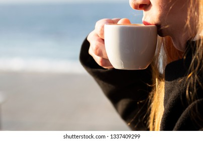 She is drinking coffee.