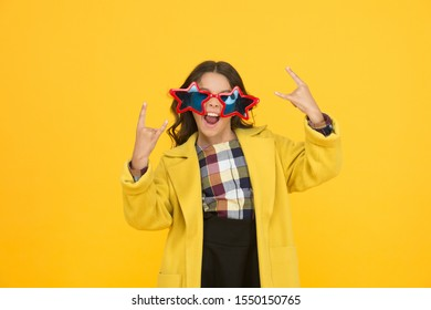 She goes crazy. Crazy child show horns sign hand gesture. Happy girl with crazy look yellow background. Fashion kid wear star shaped glasses. Crazy holiday mood. School holidays.