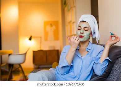She is going out tonight. Woman with face mask polishing nails at her home