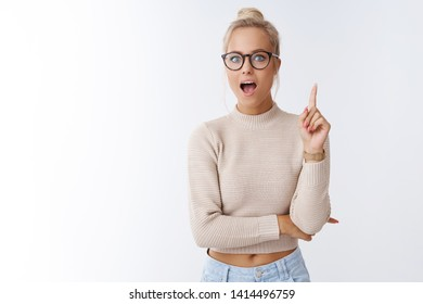 She got excellent idea. Indoor shot of enthusiastic creative young female designer adding suggestion raising index finger in eureka gesture open mouth to say plan posing over white background