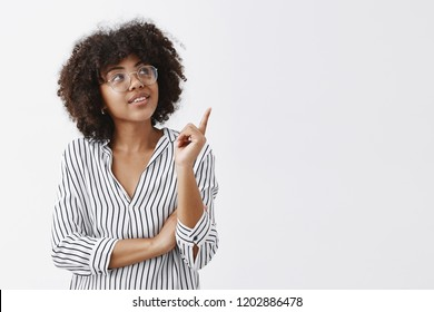She got great ideas useful for your team. Portrait of intrigued smart and stylish female in striped blouse and glasses looking and pointing at upper right corner with curious interested expression