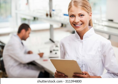 She has brilliant scientific mind. Cheerful young female scientist holding digital tablet and looking at camera while her male colleague working in the background