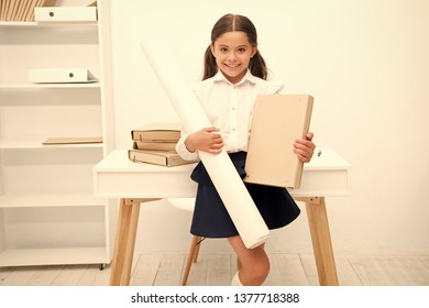 She likes creative tasks. Girl child hold folder and whatman paper while stand table white interior. Kid school uniform happy face ready with her project. Pupil creative prepared school project.