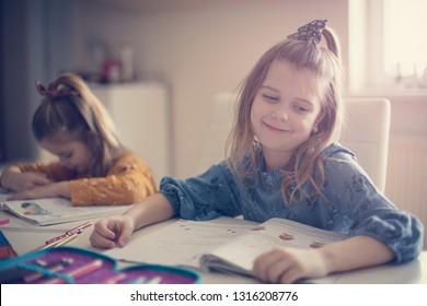 She love school obligation. Two little girls working homework together.