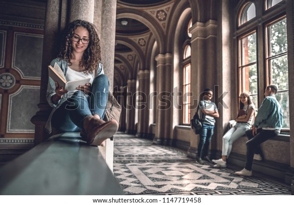 She loves reading. Beautiful female student sitting on the railing in the university and preparing for exams,when her friends on background.