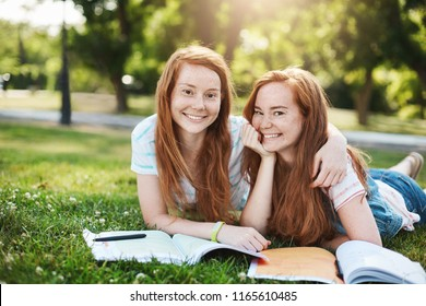 She is my partner in crime. Joyful attractive redhead girls with cute freckles hugging while lying on grass in warm summer day, doing homework and chatting, smiling at camera with happy expression