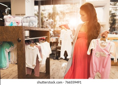 She prepares to become a mother and chooses clothes for her future child. Here a large selection of clothes for young children.