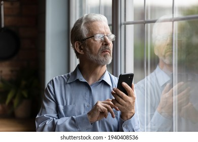 She should be back by now. Worried older man husband look at window wait for wife delayed to go back home hold phone make call. Nervous retired father feel distressed for grown child dial cell number