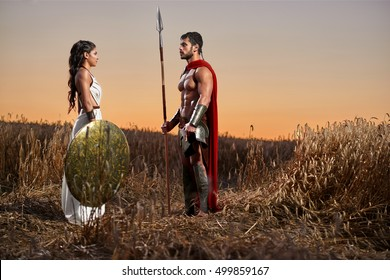 She will be waiting. Beautiful young woman in a white dress holding a shield saying goodbye to her husband handsome strong muscular Spartan warrior in a field at dusk