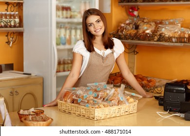 She will have you coming back for more. Gorgeous young woman leaning on a counter in her bakery smiling cheerfully to the camera