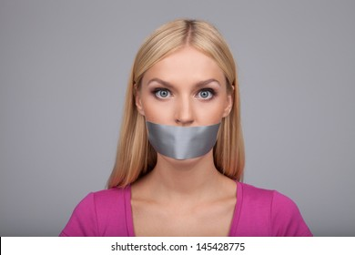 She will not gossiping anymore. Portrait of beautiful young women with her mouth covered with an adhesive tape standing isolated on gray