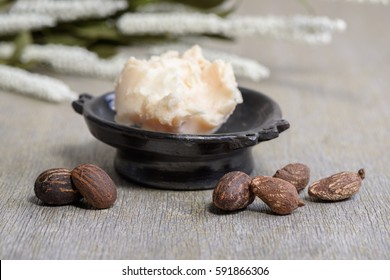 Shea butter nuts on white and a bowl of shea butter, close up