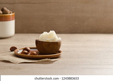 Shea butter and nuts on a wooden board, copy space.