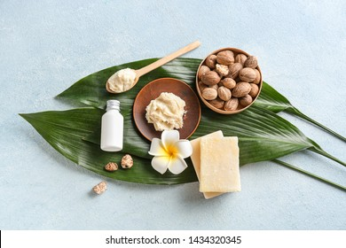 Shea butter with soap and cream on color background