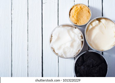 shea, macadamia nut and coffee butter, black cosmetic mud on white wooden table background