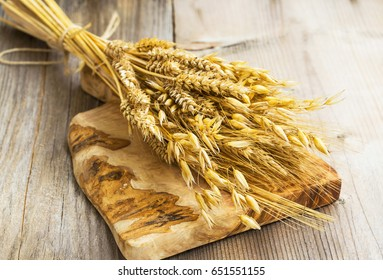 Sheaf with wheat, barley and oat ears on wooden board
