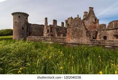 Shearington, Scotland, UK - June 18, 2012: Closeup of South side of ruined  triangular brown stone moated Caerlavarock Castle. Moat and corner tower. Yellow flowers up front.
