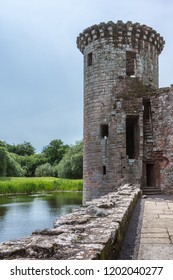 Shearington, Scotland, UK - June 18, 2012: Closeup of Southwest tower of ruined  triangular brown stone moated Caerlavarock Castle under blue sky and surrounded by moat. Seen from inside castle.