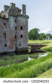 Shearington, Scotland, UK - June 18, 2012: Closeup of East side of entrance tower to ruined  triangular brown stone moated Caerlavarock Castle. Reflections in moat. Cannons on bridge.