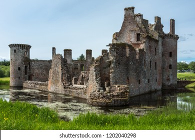 Shearington, Scotland, UK - June 18, 2012: South and East side of ruined  triangular brown stone moated Caerlavarock Castle. Moat and corner tower.