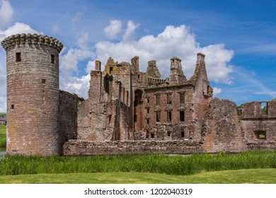 Shearington, Scotland, UK - June 18, 2012: Closeup of South side of ruined  triangular brown stone moated Caerlavarock Castle with Early Domestic Classical Architecture under blue sky. moat around