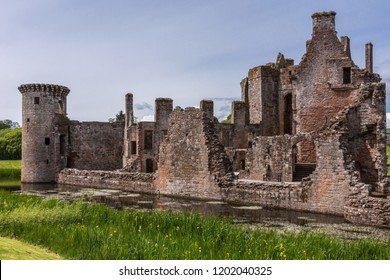 Shearington, Scotland, UK - June 18, 2012: Closeup of South side of ruined  triangular brown stone moated Caerlavarock Castle. Moat and corner tower.