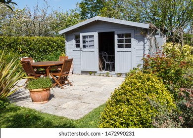 Shed with open door and terrace with wooden garden furniture during spring
