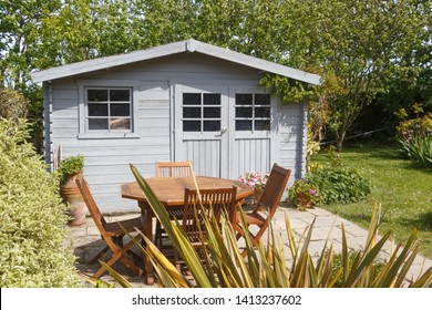 Shed with terrace and wooden garden furniture during spring