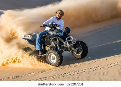 SHEDGUM - DECEMBER 19 2014: A quad bike rider creates a cloud of sand during a turn while riding in the deserts of Eastern Province, Saudi Arabia.