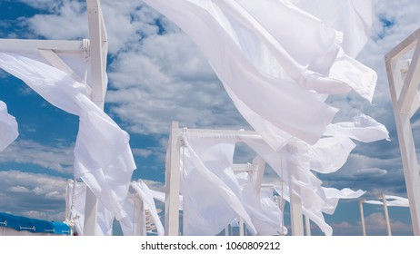 Sheds  awning with fabric white curtains on the seashore breeze in the wind