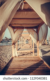 Sheds awning with white curtains on the seashore in the wind.