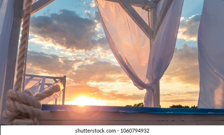 Sheds with fabric white curtains on the beach in the evening