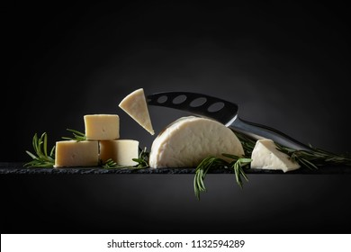Sheep cheese with rosemary and  knife on a black background.