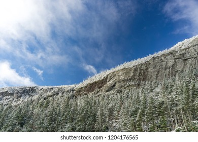 Sheer Cliff with snow covered trees and blue sky above
