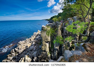 Sheer cliffs of the northern coast of Bornholm island - Helligdomsklipperne (Sanctuary Rocks), Gudhjem town in the background, Denmark