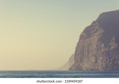 Sheer steep cliffs rising above the sea.