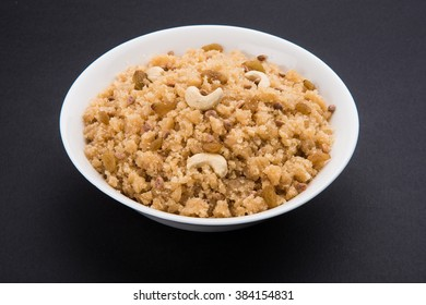 Sheera or Suji/Sooji Halwa is a semolina based sweet that originated in India. Shira is Garnished with dry fruits and served in ceramic bowl. Isolated over colourful/wooden background. Selective focus