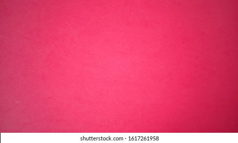 A sheet of bright pink paper with light vignetting around the edges. Intense fuchsia color. Saturated bright paint. Velvet paper texture. Background for greeting card or page. Valentine's Day