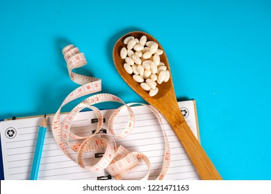 Sheet of Diet Plan and wooden spoon with a measuring tape on a blue background, diet, healthy lifestyle